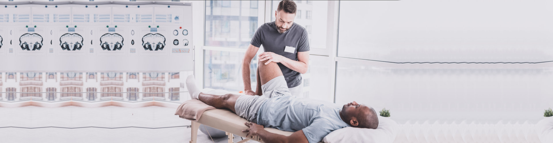 Try to relax. Pleased brunette therapist bowing head while examining his injured patient