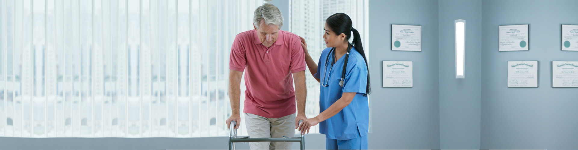 Physical therapist or doctor helping older male patient learn to walk with a walker. Female nurse assisting senior man with recovery after surgery