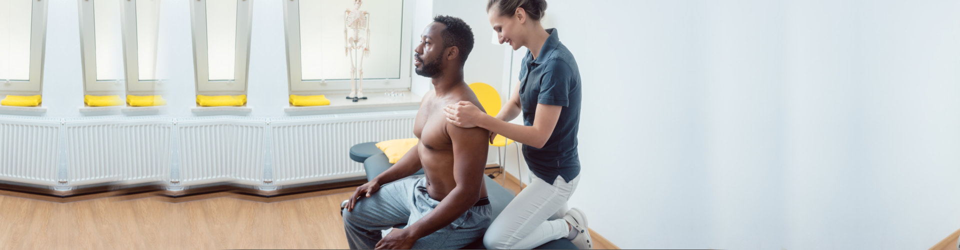 Physical therapist massaging a young black man on shoulder after a sport injury