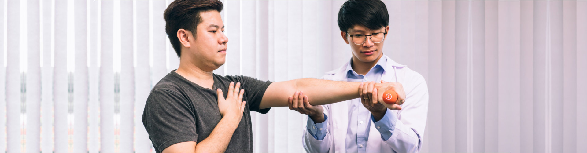 Asian young male physiotherapist helping patient with lifting dumbbells exercises in clinic.